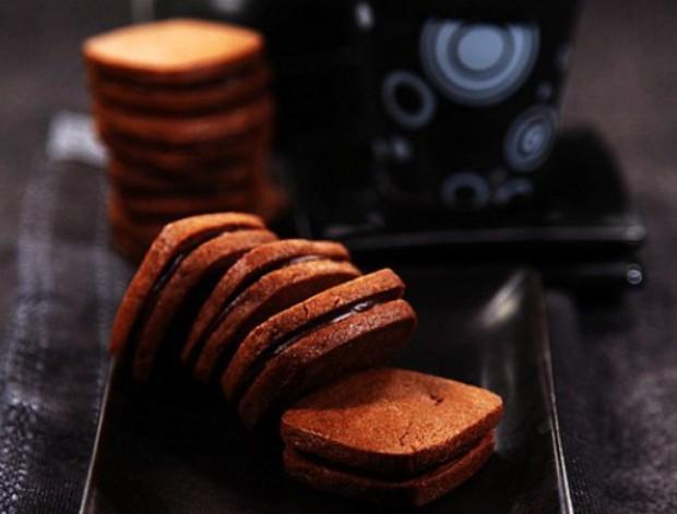 用料1 低筋面粉 100克,巧妃可可粉 12克,黄油 80克,细砂糖 40克,蛋黄 1个 用料2 (巧克力夹心) 巧妃黑巧克力 80克,黄油 20克 巧克力夹心饼干的做法: 1.将面粉与可可粉混合过筛。黄油(无需软化)切成小块放在面粉上 2.用手指将面粉与黄油丁混合并反复捏匀 3.一直捏到黄油和面粉完全融合,呈现粗玉米粉状态。这个过程可能会比较耗费时间 4.